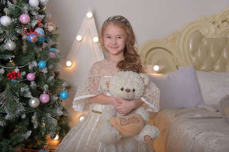 vintage portrait of a little girl in alabaster elegant dress with a toy bear in her hands