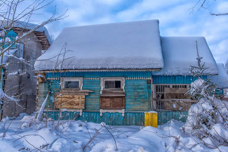 wooden house snow-covered in winter with boarded up windows