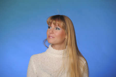 portrait of a beautiful long-haired blonde in a studio on a blue background in a white sweater