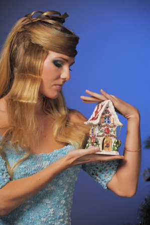 beautiful long-haired blonde in the studio with a beautiful creative hairstyle with braids holding a toy house candlestick in hands, christmas concept