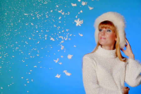 beautiful long-haired blonde in the studio in a white fur hat in the studio on a blue background and snow