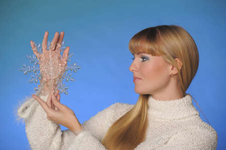 beautiful long-haired blonde in the studio on a blue background with a snowflake in her hands, winter concept