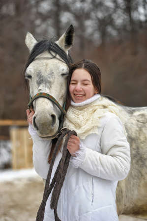 girl in a white coat in winter with a horse portrait 免版税图像