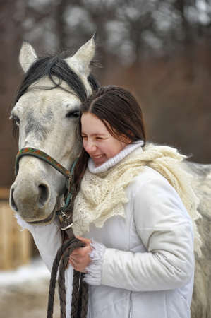 girl in a white coat in winter with a horse portrait
