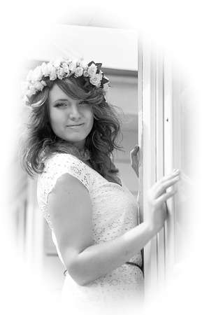 beautiful young brunette in a wreath of white flowers on an alley in summer Stock fotó