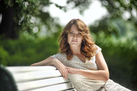 beautiful young brunette in summer in a white dress sits on a park bench Stockfoto