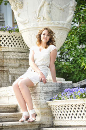 beautiful young brunette in summer in a white dress in a park with pansies in the flowerbed Zdjęcie Seryjne