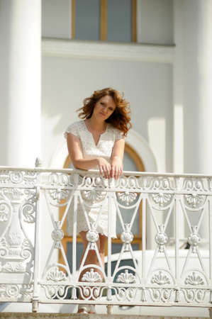 beautiful young brunette in the summer on a walk near the railing in the park Zdjęcie Seryjne