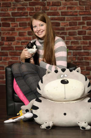 pretty smiling girl on a background of a brick wall with a black and white cat in hands
