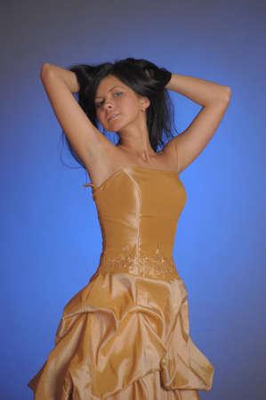 nice brunette girl in a long golden dress in the studio Stockfoto