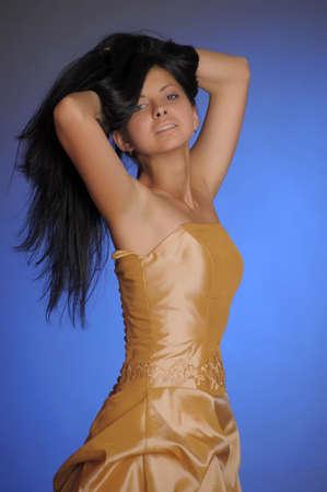 nice brunette girl in a long golden dress in the studio