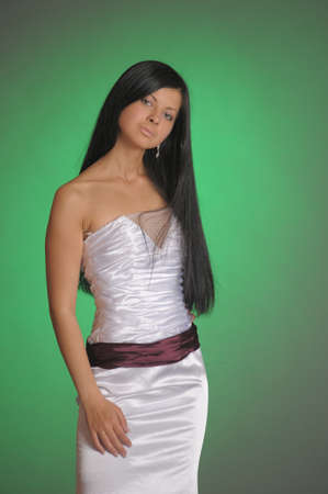nice brunette girl in a long white dress in the studio on a green background
