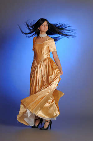 nice brunette girl in a long golden dress in the studio