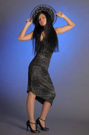 nice brunette girl in a black dress and a witch hat on a blue background in the studio