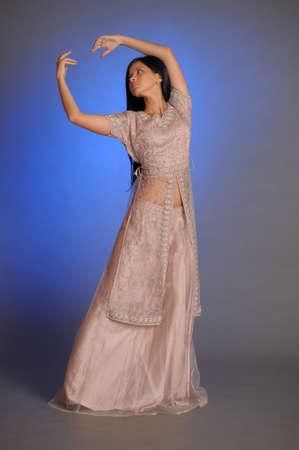 nice brunette girl in oriental dress on a blue background in the studio