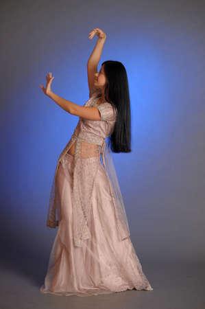 nice brunette girl in oriental dress on a blue background in the studio Imagens