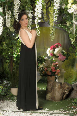 brunette in a long evening dress in a greenhouse among flowers Stock fotó