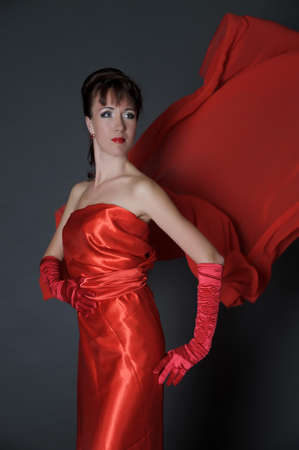 elegant brunette in a red dress on a gray background in the studio and fluttering fabric Фото со стока