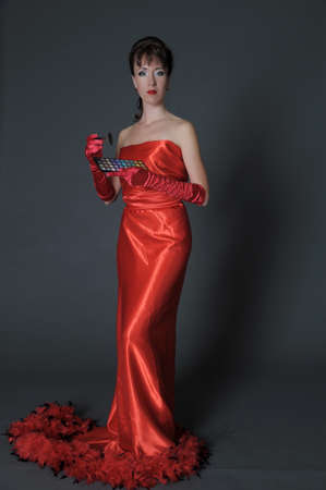 elegant brunette in a long red dress on a gray background in the studio with a palette of eyeshadows and a brush for makeup in hands