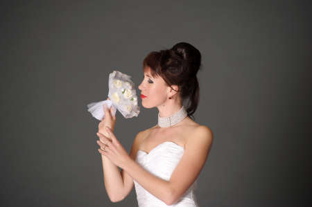 elegant brunette in a white wedding dress in the studio on a gray background with a wedding bouquet in her hands Stok Fotoğraf