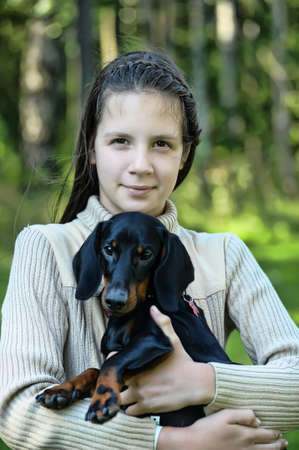 portrait of a girl with a dachshund in hands