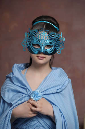 girl in blue vintage dress with carnival mask