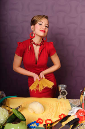 sexy housewife in a red dress with pasta in her hands