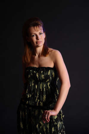 blonde in a camouflage dress coloring on a dark background in the studio