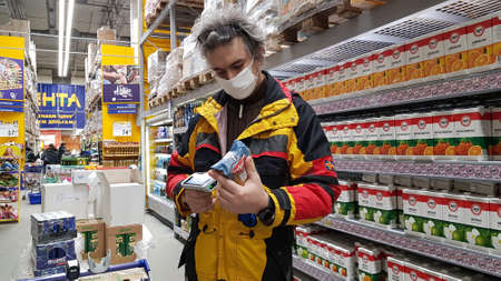 Russia, St. Petersburg 14.03.2020 Buyer with a hand scanner in his hands and a medical mask on his face in a supermarket