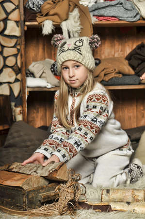blonde girl in knitted clothes and a hat with pompons