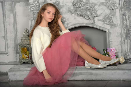a beautiful pensive girl in a white sweater and pink skirt with flowers by the fireplace