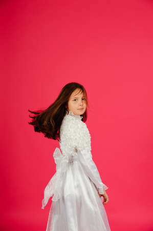 child girl in a white dress on a pink background