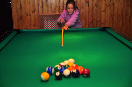 little girl with a cue in hands plays billiards
