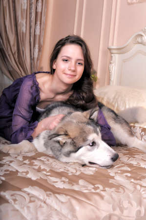young girl in a lilac dress with her malamute in bed
