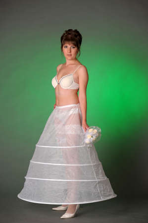 brunette bride in the morning in bra, crinoline and wedding bouquet in hand, preparing the bride