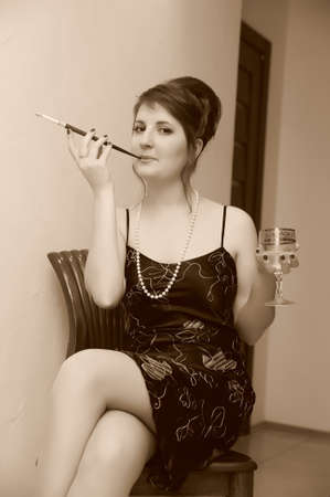 a woman in a black dress is sitting on a chair with a glass in her hand and a cigarette with a mouthpiece Stock Photo