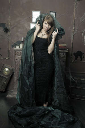 beautiful brunette woman in a black dress and a green cape, vintage photo
