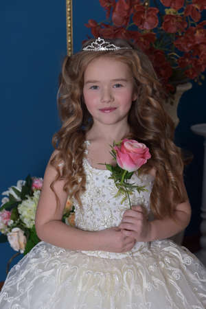 young princess in a white dress with a diadem and a rose in her hands Stock Photo