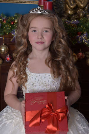 young princess in a white dress with a diadem with a box with a gift in her hands in Christmas