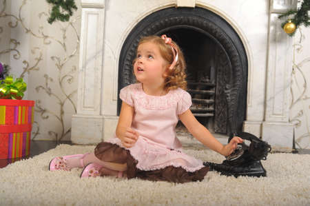 little girl sitting next to a vintage black telephone