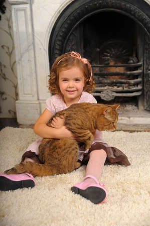 happy little girl with a cat in her arms Imagens