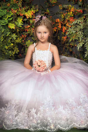 little girl princess in elegant white vintage dress with a bouquet of flowers