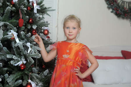 little cute girl blonde in orange dress by the christmas tree