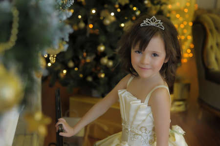 little cute girl young princess in a chic white Christmas dress by the golden Christmas tree 免版税图像
