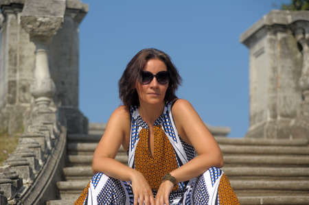 brunette woman in summer in the park with sun-glasses sits on stone steps