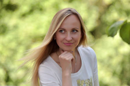 portrait of a 30-year-old blonde against a background in the park