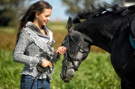 beautiful young brunette with gray horse in a field in summer