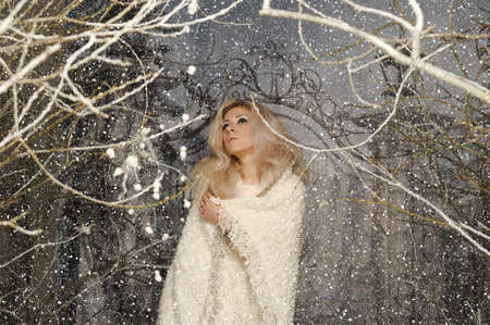 blonde girl wrapped in a plaid in winter. snow covered trees