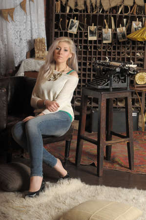 blonde in a white sweater with beads around her neck sits in a clasp 免版税图像