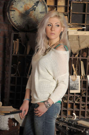 blonde in a white sweater with beads around her neck in the interior of the room 免版税图像